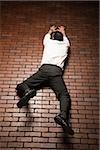 man climbing up a brick wall