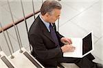 Businessman using laptop on stairs, Munich, Bavaria, Germany