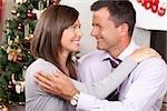 Couple embracing at Christmas tree