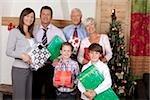 Grands-parents, parents et enfants tenant des cadeaux de Noël
