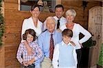 Grands-parents, les parents et les enfants devant la maison en bois