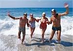 Two exuberant senior couples in the ocean