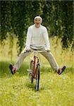 Laughing senior man riding bike in meadow