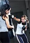 Two women boxing with sandbag
