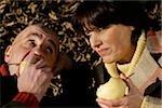 Couple d'âge mûr se trouvant sur les feuilles et manger des poires