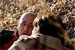 Couple d'âge mûr se trouvant sur les feuilles et parler