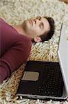 Young Man liegend auf einem Teppich neben einem Laptop schlafen - Müdigkeit - Entspannung - Technology - Home - Wohnzimmer