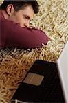 Young Man liegend auf einem Teppich neben einem Laptop - Müdigkeit - Entspannung - Technology - Home - Wohnzimmer
