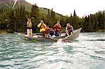 Woman battling trout on Kenai River from drift boat Kenai Peninsula Alaska Summer