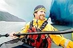 Man kayaking amongst large icebergs near Bear Glacier in Resurrection Bay near Seward, Alaska