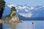 Sea kayaker in Lynn Canal near rocky coastline w/Herbert Glacier background Southeast Alaska