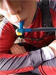 Female hiker takes drink from hydration pack Kenai Peninsula Alaska summer