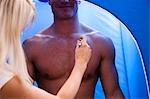 Close up of a man getting a fake tan with an airbrush gun