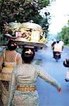 Femme (femmes) en robe brodée avec des offrandes du temple marche sur une route avec des motocyclistes dans le lointain. Ubud, Bali, Indonésie.