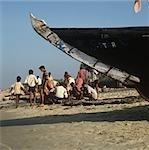 Fishermen sorting fish under boat,Goa,India.