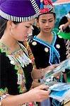 Filles Hmong en costume traditionnel en regardant des photos d'eux-mêmes à la nouvelle année festival, Phonsavan, Laos