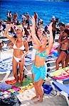 Women wearing bikinis dancing on beach,San Antonio,Ibiza,Balearic Islands,Spain