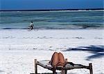 Tourist on sun lounger and cyclist,Matemwe beach,Zanzibar,Tanzania