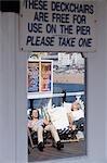 Two girls sunbathe on Brighton Pier,Summer,English seaside,Brighton,East Sussex. England,UK