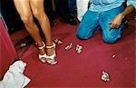 Strip club ( stripclub ),woman ' s legs with cash ( dollars ) on the floor and a man kneeling . South Beach,Miami,USA .