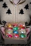 Femme tenant boîte de décorations de Noël