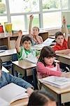 Kinder in Grade drei Klassenzimmer, die Hände heben