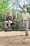 Grandfather Pushing Grandson on Swing