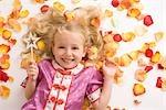 Little Girl with Magic Wand Lying Amongst Flower Petals