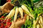 Personne qui détient des légumes au marché