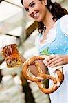 Junge Frau mit Glas Bier und Brezel