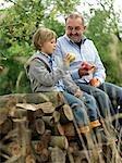Man and boy avec pommes, assis sur les billes
