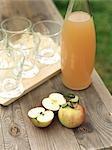 Pommes, jus de pomme et les verres sur la table