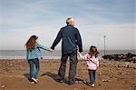 mature man with children on beach