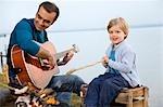 boy,man with guitar roasting sausages
