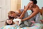 couple jouant au lit avec une fille