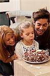 parents et enfant soufflant des bougies