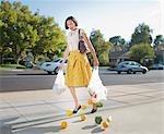 Woman dropping groceries on sidewalk