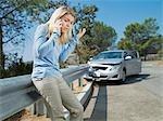Frustrierten Frau mit Handy neben Auto zerstört auf Geländer