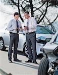 Zwei Geschäftsleute, die Austausch von Informationen über beschädigte Autos