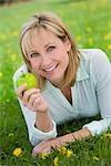 Woman Lying in Meadow Holding an Apple