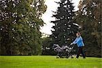Woman Pushing Stroller in Park, Seattle, Washington, USA