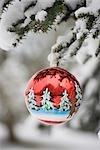 Ornement de Noël coloré accroché à une branche couverte de neige