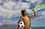 Jeune garçon vuvuzela de soufflage et de tenir le ballon sous le bras, montagne de la Table dans le fond, affichage de la Table, Cape Town, Province occidentale du Cap, en Afrique du Sud