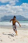 Garçon jouant avec ballon de football sur la plage, la montagne de la Table dans le fond, affichage de la Table, Cape Town, Province occidentale du Cap, en Afrique du Sud