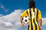 Vue arrière du footballeur tenant le ballon sous le bras, vue de la Table, Cape Town, Province occidentale du Cap, en Afrique du Sud