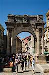 Les touristes se promenant dans la pierre en arc dans la vieille ville, Pula, Côte d'Istrie, en Croatie, Europe