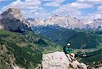 Randonneur au repos au sentier de l'Alta Via Dolomiti (Via Ferrata) avec Corvara village ci-dessous, Dolomites, Haut-Adige, Italie, Europe