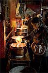 Femme ajoutant la fonte yak beurre de sa lampe à ceux du temple, Meru Nyingba monastère, Bharkor, Lhassa, Tibet, Chine, Asie