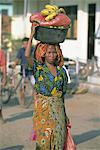 Woman carrying basket of fruit on her head, Sape, Sumbawa, Nusa Tenggara group, Indonesia, Southeast Asia, Asia