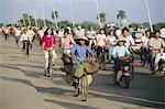 Cyclists in morning rush hour on Phu Xuan bridge, Hue, Vietnam, Indochina, Southeast Asia, Asia